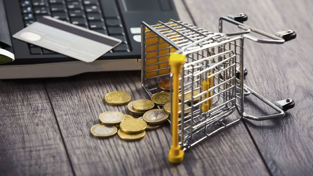 Abandoned Shopping Cart mini figure with coins next to open laptop