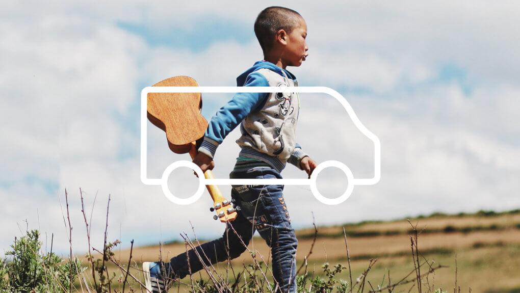 kid running in a field holding a ukulele, with an overlay of a van icon