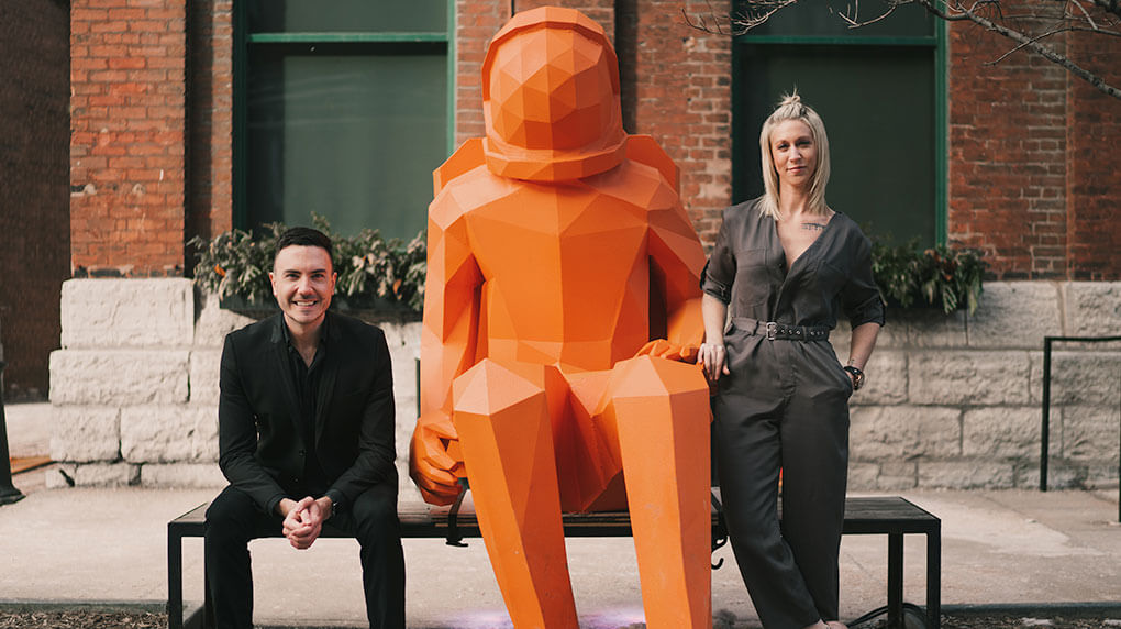 Mitchell and Lauren standing next to an astronaut statue