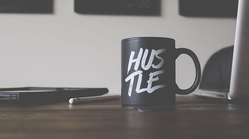 black mug with  text Hustle on the desk