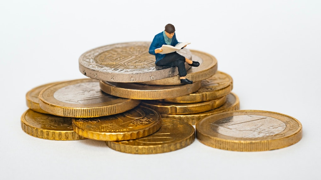 small figurine man reading newspaper on a stack of coins