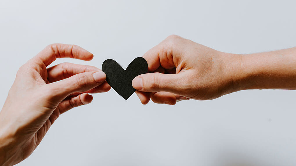 two people sharing a small black paper heart