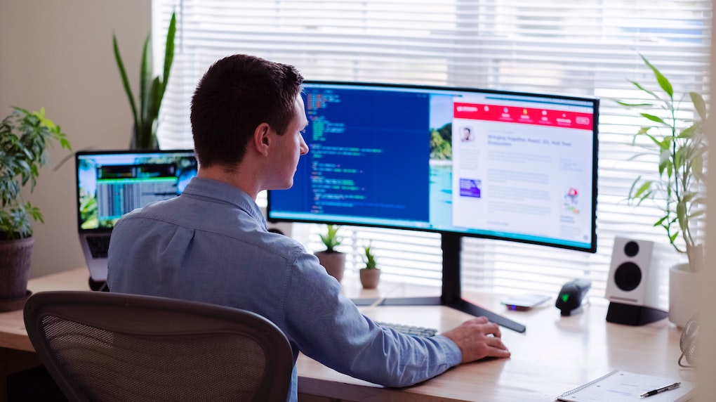 man with two screens working at home